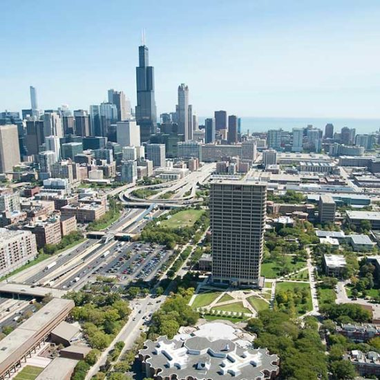 An aerial view of UIC's campus, showing the the College of Education building, the Biological Sciences building and University Hall, with the Chicago skyline in the background.