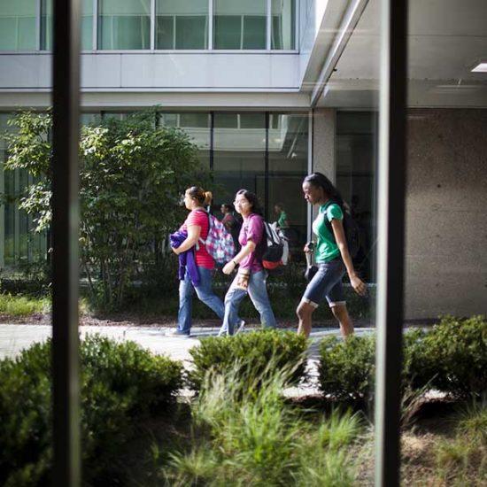 Three female students walk past Douglas Hall.