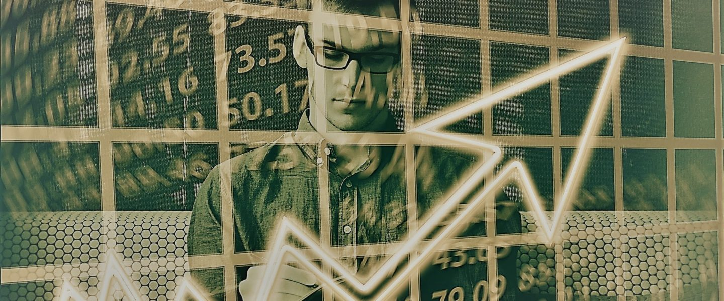 A graphical image shows a male student in the background writing on a notepad.  In the foreground, there are graphical images of a stock market chart and stock market prices.