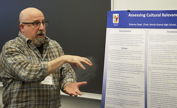 Doctoral student Phil Cantor gestures as he presents research findings, standing in front of a poster outlining his research.