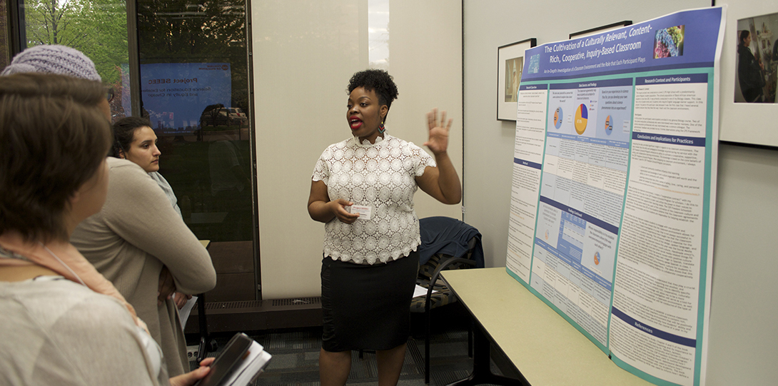 Master Teaching Fellow Mindy Chappell stands in front of her poster, explaining her research to a group of Project SEEEC fellows standing in front of her.