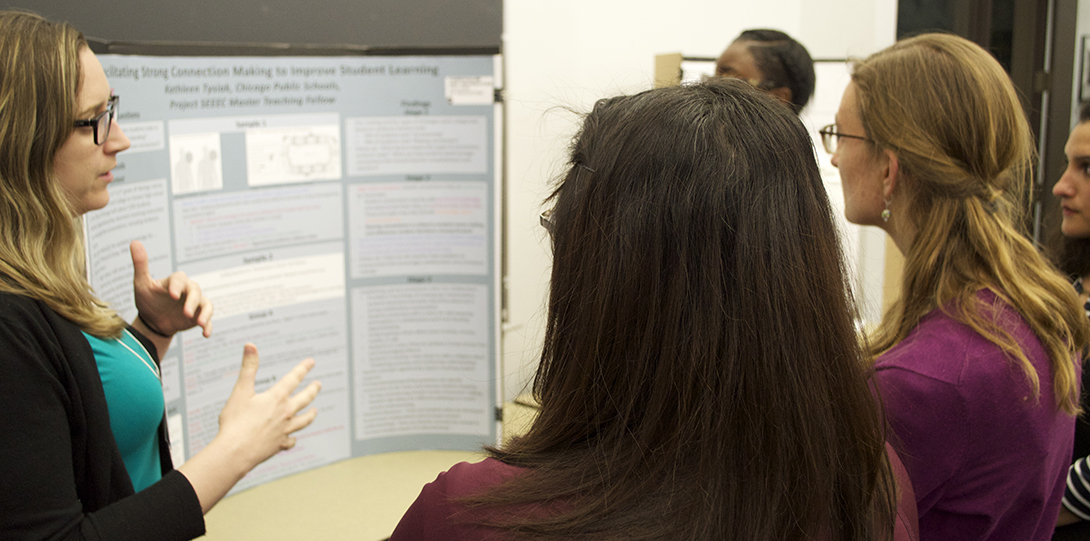 Master Teaching Fellow Kathleen Tysiak stands in front of her research poster, explaining her findings to peer fellows standing in front of her.