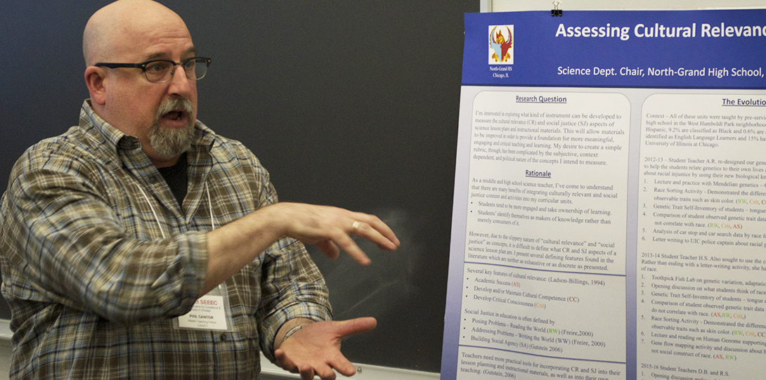 Master Teaching Fellow Phil Cantor gestures with both hands while standing in front of her poster, explaining his research.