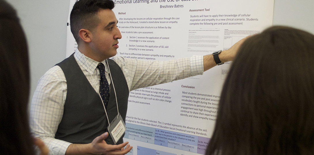 Master Teaching Fellow Brehznev Batres points to a poster detailing his research as SEEEC teaching fellows listen to his presentation.