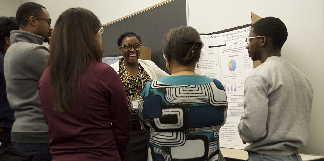 A group of SEEEC teaching fellows stand in front of a poster, having a conversation about the research presented.