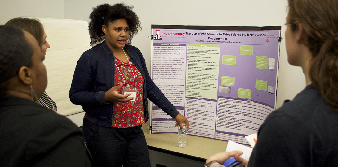 Master Teaching Fellow Tiffany Childress Price stands in front of her research poster, explaining her findings to peer fellows standing in front of her.