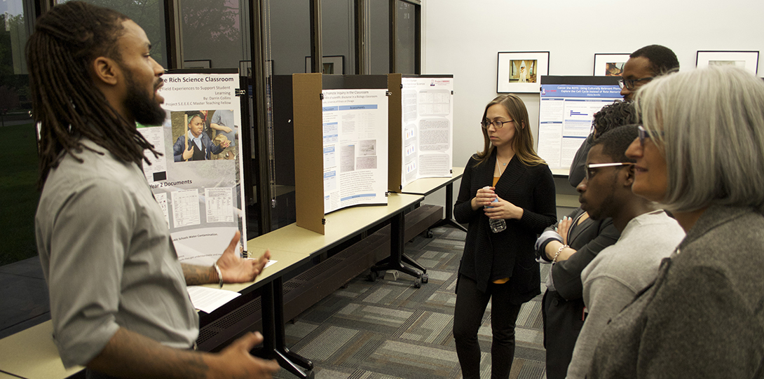 Master Teaching Fellow Darrin Collins stands in front of his research poster, explaining his findings to peer fellows standing in front of him.