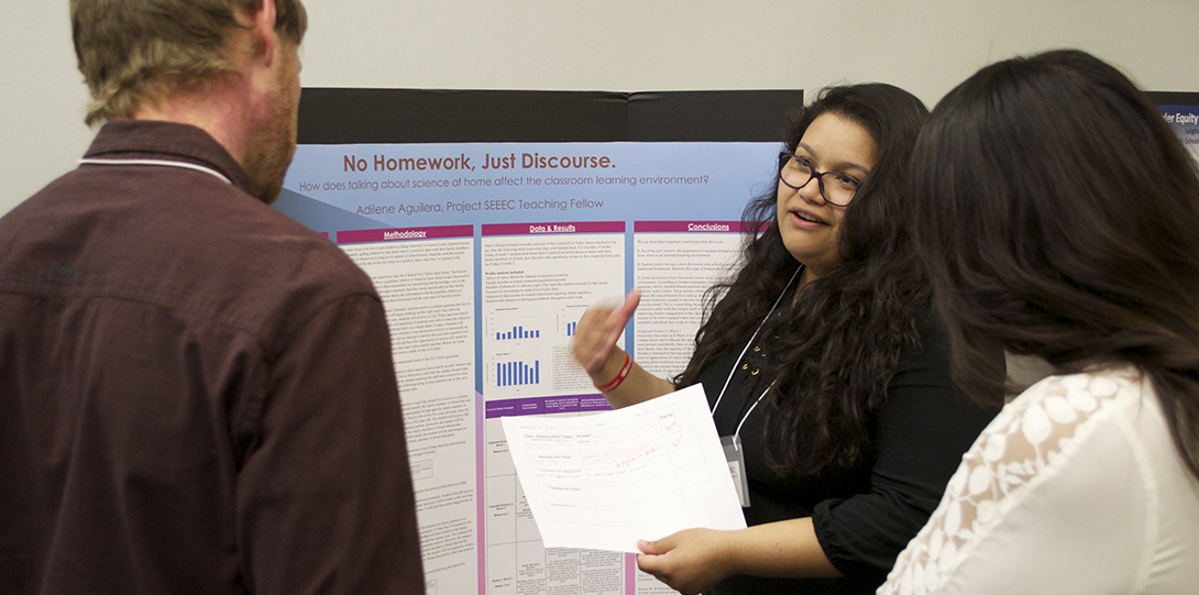 SEEEC Teaching Fellow Adilene Aguilera gestures to two other fellows while explaining her poster presentation.