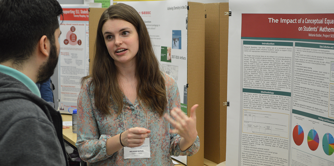 SEEEC Teaching Fellow Melanie Butler gestures with her hands while explaining her poster presentation to another fellow.
