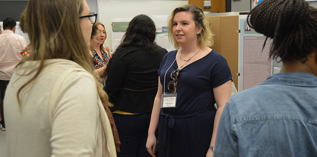 SEEEC Teaching Fellow Erin Cathcara talks with other fellows about her research project, with presentation posters behind her.