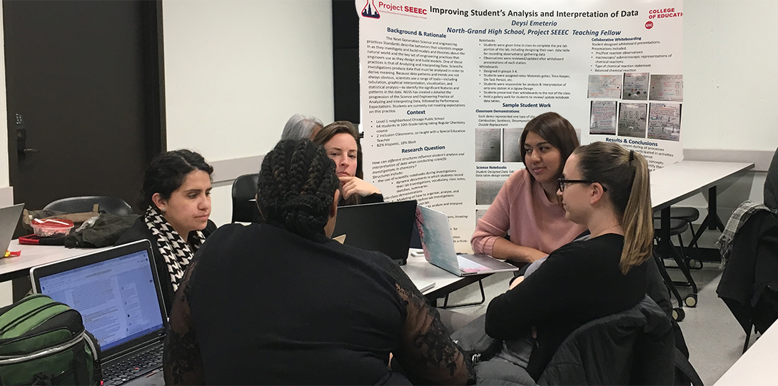 SEEEC Teaching Fellow Deysi Emeterio sits at a table with other fellows, discussing her research.  Her poster presentation is behind her.