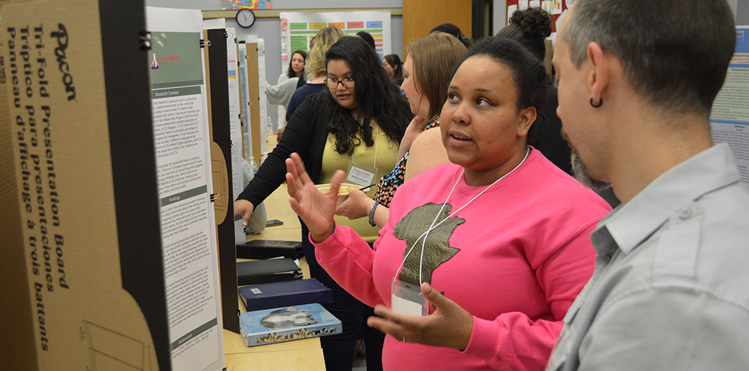 SEEEC Teaching Fellow Michele Drayton gestures with her hands while explaining her poster presentation to professor Danny Morales-Doyle.