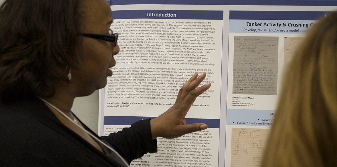 Master Teaching Fellow Nina Hike gestures toward her poster presentation while explaining her research to a teaching fellow.