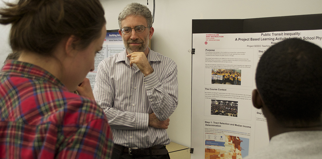 SEEEC Teaching Fellow Ross Hyman listens to a fellow student while explaining her poster presentation.
