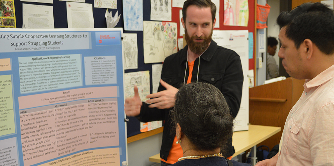 SEEEC Teaching Fellow Brian Lampert gestures with her hands while explaining her poster presentation to other fellows.