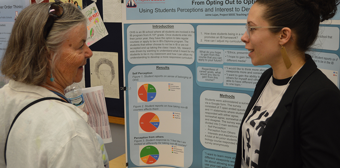 SEEEC Teaching Fellow Jamie Lujan explains her poster presentation to a Project SEEEC researcher.