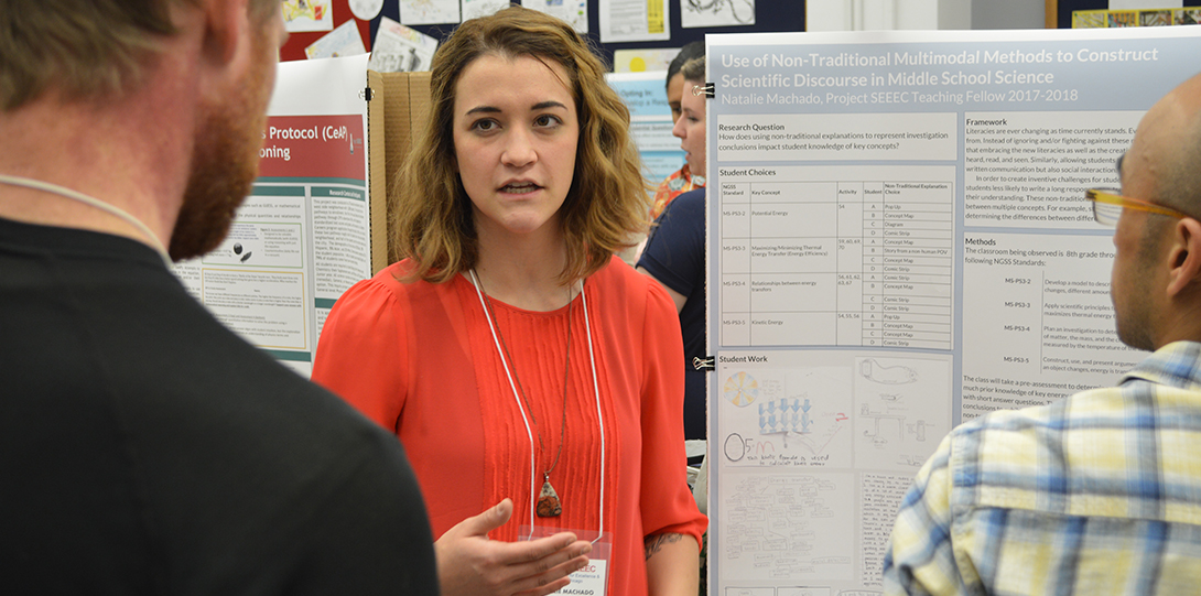 SEEEC Teaching Fellow Natalie Machado gestures with her hands while explaining her poster presentation to another fellow.