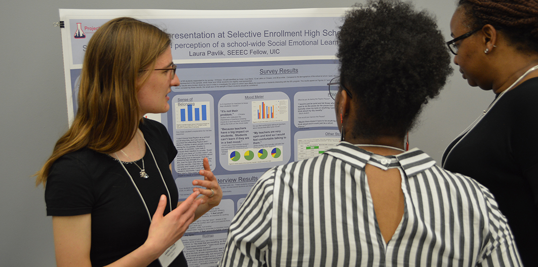 SEEEC Teaching Fellow Laura Pavlik gestures with her hands while explaining her poster presentation to other fellows.