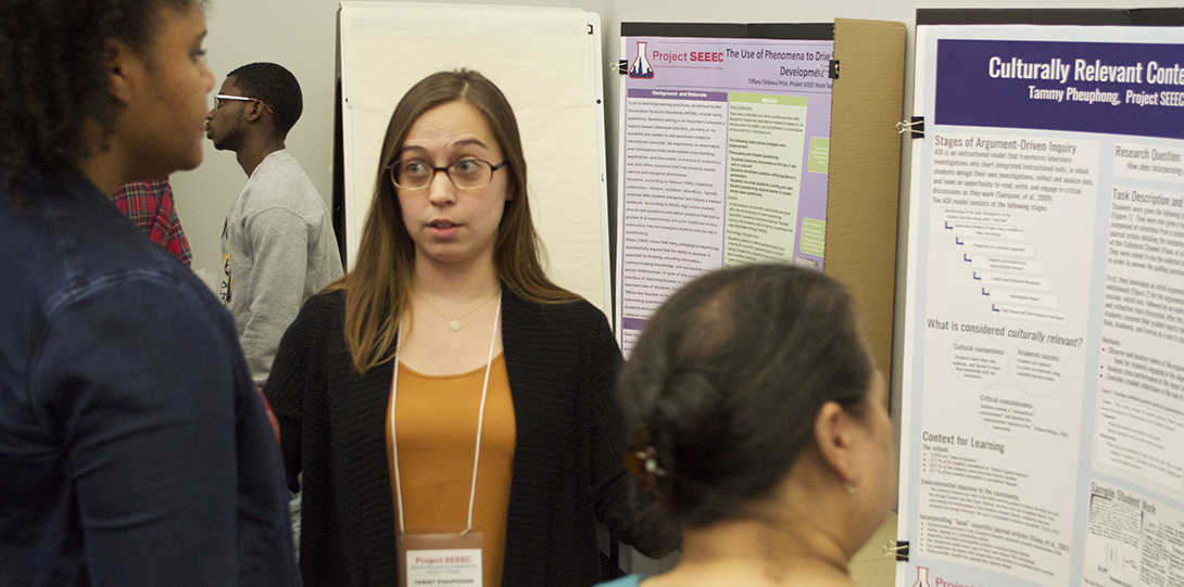SEEEC Teaching Fellow Tammy Pheuphong talks with a fellow student while standing in front of her poster presentation.