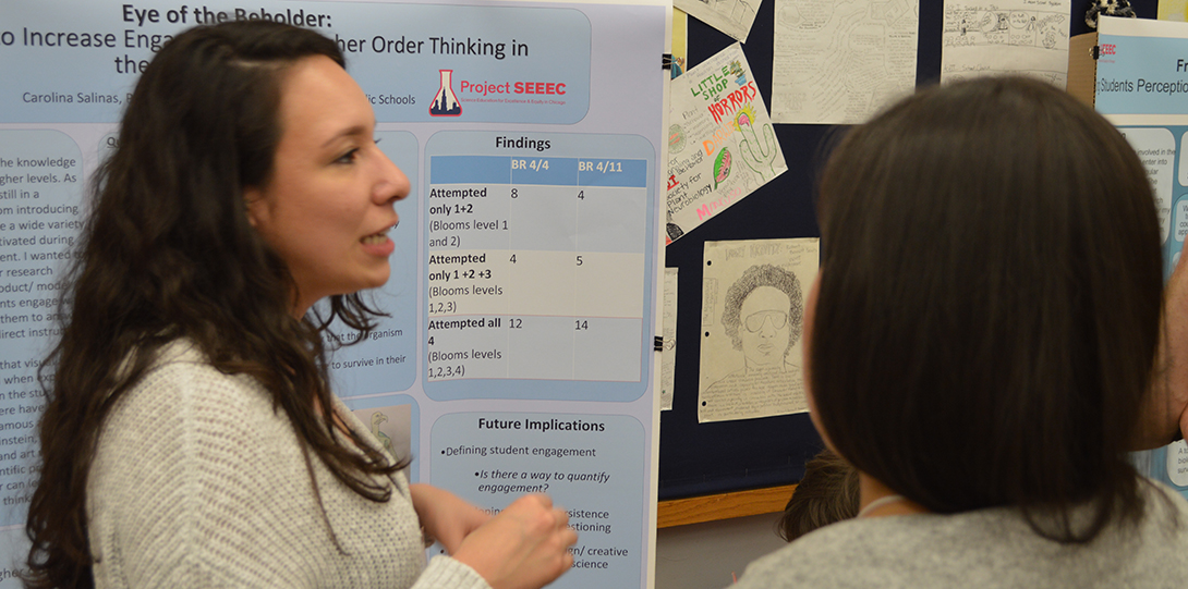 SEEEC Teaching Fellow Carolina Salinas converses with other fellows while standing in front of her poster presentation.