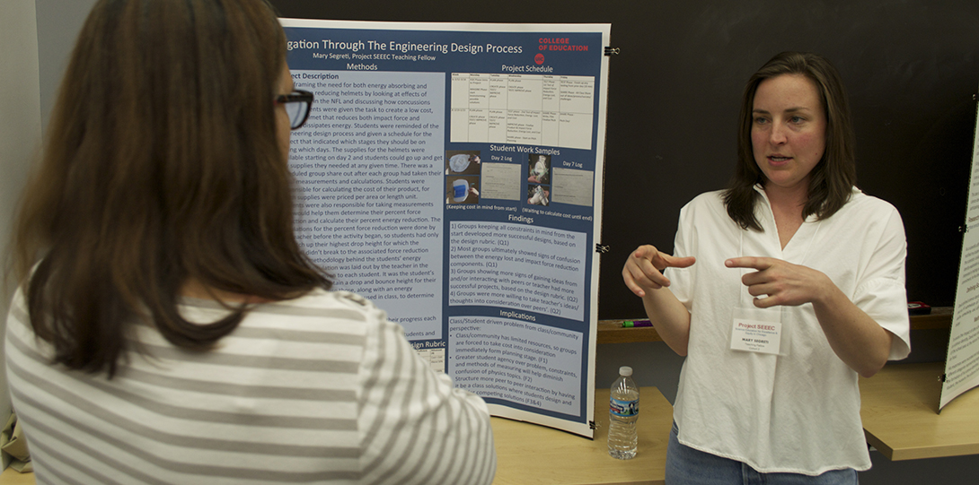 SEEEC Teaching Fellow Mary Segreti gestures with her hands while explaining her poster presentation to another fellow.