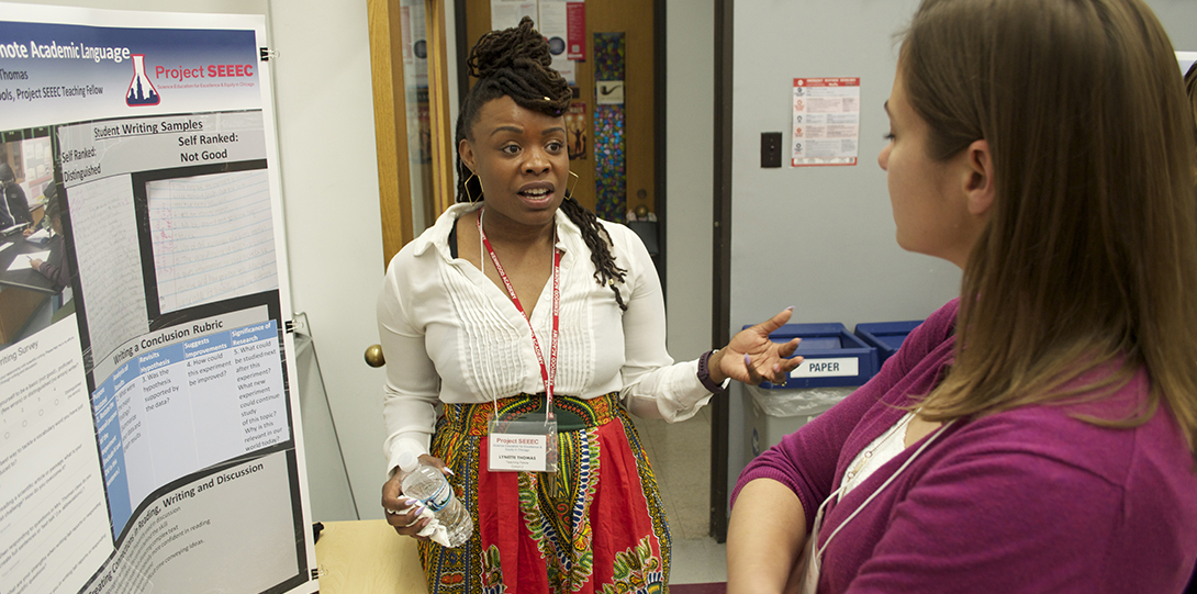 SEEEC Teaching Fellow Lynette Thomas gestures with her hands while explaining her poster presentation to another fellow.