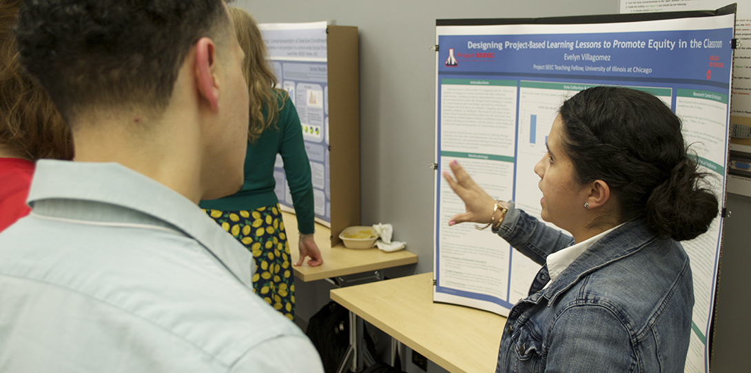 SEEEC Teaching Fellow Evelyn Villagomez gestures with her hands while explaining her poster presentation to another fellow.