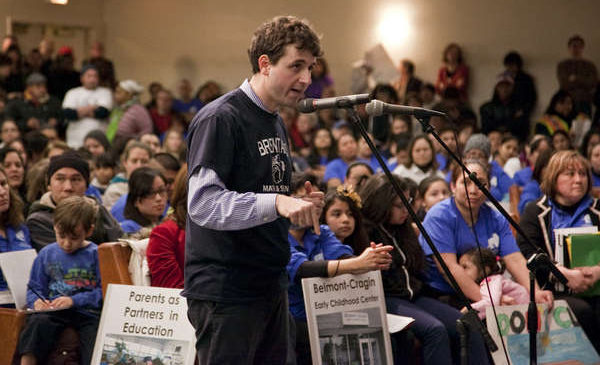 Alumnus principal Seth Lavin speaks into a microphone at a Chicago school board meeting, with a large crowd behind him.