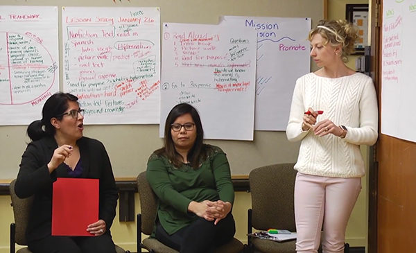 Three teachers are discussing curriculum planning, with a series of white poster sheets behind them filled with notes.