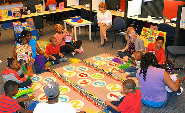 A sutdent in the PhD Literacy, Language and Culture program leads a workshop for young parents and their toddlers at the UIC Reading Clinic.  The group is sitting in a circle and singing a song to the toddlers.