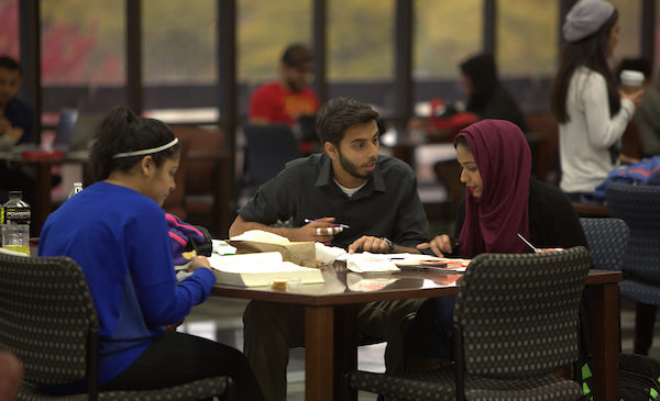A male and female student discuss their homework sitting at a table in the UIC library.
