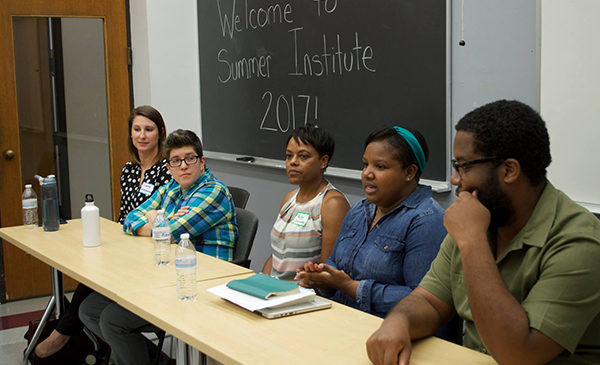 Doctoral alumni and college faculty sit at a table at the front of a classroom, leading a discussion during a PhD Special Education summer institute.