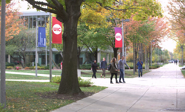 Students walk down a sidewalk on UIC's campus, with UIC banners flanking the sidewalk.