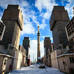 A smokestack rises up to the sky with an abandoned Chicago factory in the foreground.
